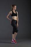 亭亭玉立的女性的身体做在灰色低调,完善的金发碧眼的女人的activewear的posin 库存照片