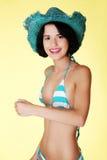 年轻亭亭玉立的妇女佩带的游泳衣和夏天帽子 图库摄影