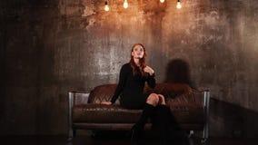 亭亭玉立的妇女在一个沙发休息在演播室,微笑着并且看支持 股票视频