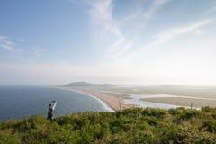 年轻亭亭玉立的妇女在高小山站立并且拍摄了海和海岸的一个宏伟的视图 免版税库存图片