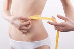 亭亭玉立的妇女测量的腰部 免版税库存照片