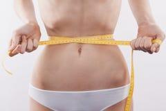 亭亭玉立的妇女测量的腰部 库存照片