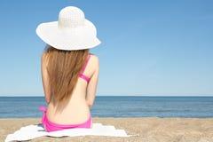 年轻亭亭玉立的妇女背面图坐沙滩 库存图片