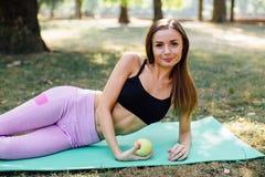 年轻亭亭玉立的妇女食用快餐在解决以后户外在公园 坐草,吃在新鲜空气的水多的苹果 免版税库存图片