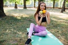 年轻亭亭玉立的妇女食用快餐在解决以后户外在公园 坐草,吃在新鲜空气的水多的苹果 图库摄影