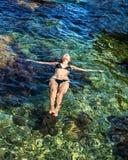 年轻亭亭玉立的妇女说谎透明海水表面上  免版税库存照片