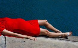 亭亭玉立的小的怀孕的夫人鼓起 躺下在红色礼服  免版税库存图片