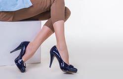 亭亭玉立的少妇的腿时髦的高跟鞋的坐白色背景 免版税库存照片