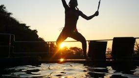 亭亭玉立的年轻女人剪影在游泳场跳跃在令人惊讶的日落通过与透镜火光作用的太阳 股票录像