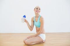 年轻亭亭玉立的拿着体育瓶的妇女佩带的运动服 库存照片