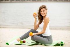 亭亭玉立的深色的女孩在一个温暖的大风天在她的选址在一含沙的瑜伽席子的手上拿着果子 免版税图库摄影