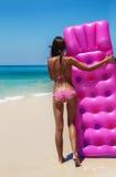 亭亭玉立的深色的妇女晒日光浴与气垫 免版税库存图片