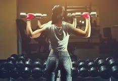 亭亭玉立的爱好健美者女孩举站立在镜子前面的重的哑铃,当训练在健身房时 免版税图库摄影
