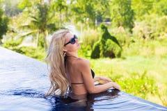 亭亭玉立的白肤金发的妇女在游泳池附近得到晒黑 免版税库存照片