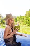 年轻亭亭玉立的白肤金发的妇女帽子喝健康戒毒所椰子汁 免版税库存照片