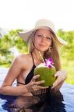 年轻亭亭玉立的白肤金发的妇女帽子喝健康椰子汁 免版税图库摄影