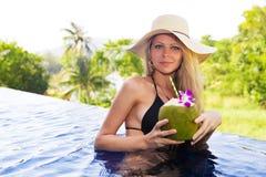 年轻亭亭玉立的白肤金发的妇女帽子喝健康椰子汁 免版税库存图片