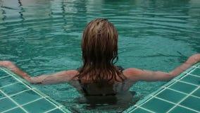 亭亭玉立的美丽的妇女进入旅馆游泳池和caming  暑假概念 股票录像