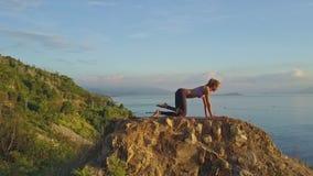 亭亭玉立的运动女孩在早晨做在峭壁的锻炼 股票录像