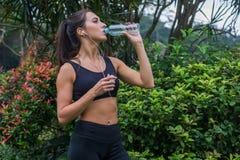 亭亭玉立的运动的女孩饮用水 休假的健身少妇在训练以后在公园 库存照片