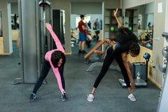亭亭玉立的黑人非裔美国人的健身辅导员显示给亚裔可爱的妇女如何做锻炼 健身房背景 库存图片