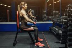 亭亭玉立,爱好健美者女孩,举站立在镜子前面的重的哑铃,当训练在健身房时 库存照片
