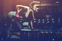 亭亭玉立,爱好健美者女孩,举站立在镜子前面的重的哑铃,当训练在健身房时 免版税库存照片