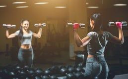 亭亭玉立,爱好健美者女孩,举站立在镜子前面的重的哑铃,当训练在健身房时 免版税库存图片