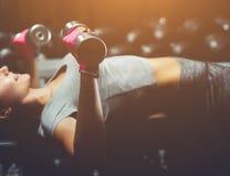亭亭玉立,爱好健美者女孩,举站立在镜子前面的重的哑铃,当训练在健身房时 免版税图库摄影