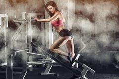 亭亭玉立,爱好健美者女孩,做在健身房的锻炼 图库摄影