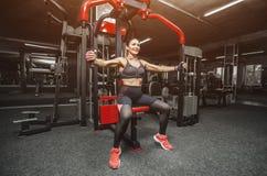 亭亭玉立,爱好健美者女孩,做胳膊的锻炼在健身房 库存图片