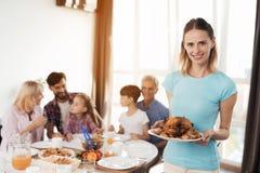 亲人的可口晚餐 妇女烹调了她的亲戚的一只芳香被烘烤的鸡 免版税库存照片