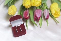 亲人的礼物 黄色和桃红色郁金香花束驱散轻的表面上 附近一个开放天鹅绒箱子红色col 库存图片