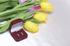 亲人的礼物 黄色和桃红色郁金香花束驱散轻的表面上 附近一个开放天鹅绒箱子红色col 免版税图库摄影