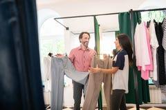 亲切的顾问助理有选择的新的裤子顾客 免版税库存照片
