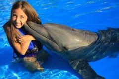亲吻一个华美的海豚鸭脚板微笑的面孔愉快的孩子的小女孩孩子游泳瓶鼻子海豚 免版税库存图片