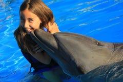亲吻一个华美的海豚鸭脚板微笑的面孔愉快的孩子的小女孩孩子游泳瓶鼻子海豚 免版税图库摄影
