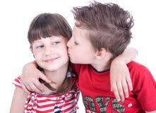 亲吻一个好女孩的逗人喜爱的男孩 库存图片