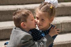 亲吻一个更老的女孩的小男孩 免版税图库摄影