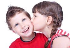 亲吻一个蓝眼睛的男孩的逗人喜爱的女孩 库存照片