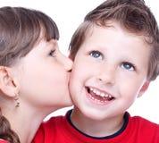 亲吻一个蓝眼睛的男孩的逗人喜爱的女孩 免版税库存图片