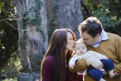 亲吻他们新的婴孩的母亲和父亲 免版税库存照片