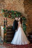 亲吻他微笑的新娘的爱恋的新郎 免版税库存照片