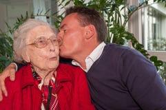 亲吻他的祖母的年轻人 免版税库存照片