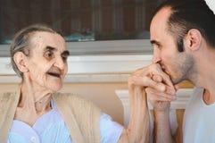 亲吻他的祖母的手的Grandsond,显示他的尊敬和爱 库存图片