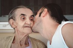 亲吻他的祖母的面颊的Grandsond,显示他的尊敬和爱 库存图片