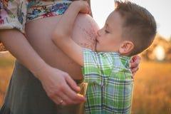 亲吻他的逗人喜爱的男孩照顾怀孕的腹部 库存图片