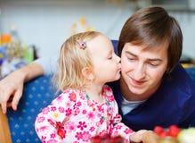 亲吻可爱的父亲的女孩她一点 免版税图库摄影