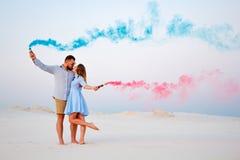 亲吻和在手上拿着彩色烟幕,浪漫加上蓝色颜色和红颜色在海滩的年轻夫妇烟幕弹 库存图片