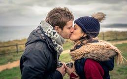 亲吻和拿着杯子热的饮料的年轻夫妇户外 免版税库存照片